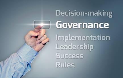 Man's hand pushing an onscreen button with the words decision-making, governance, implemeantion, leadership, success and rules listed on the screen vertically